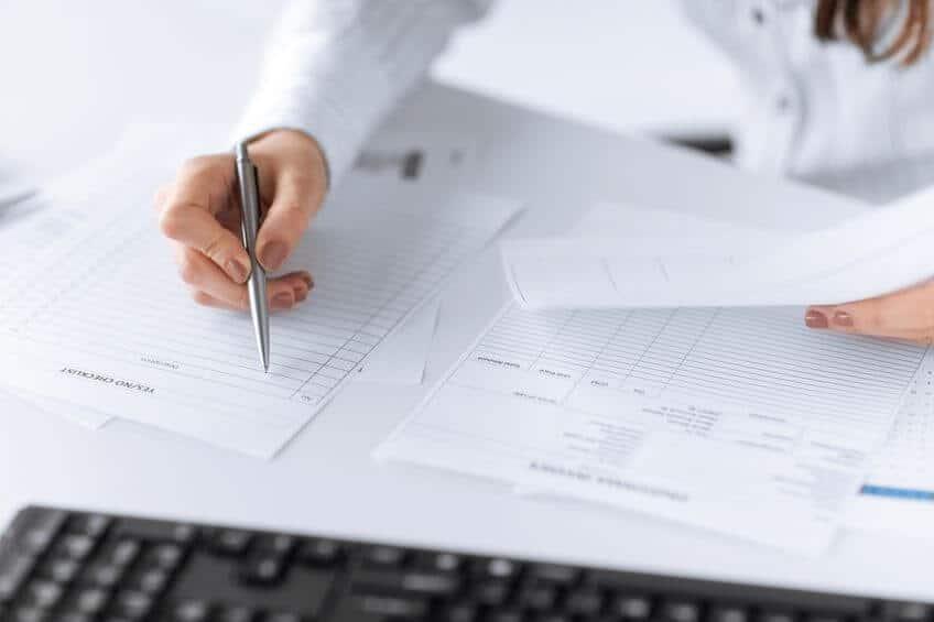 Frau, die mit der rechten Hand ein leeres Buchhaltungs-Formular ausfüllt für einfachere Finanzbuchhaltung des Kassenbuchs