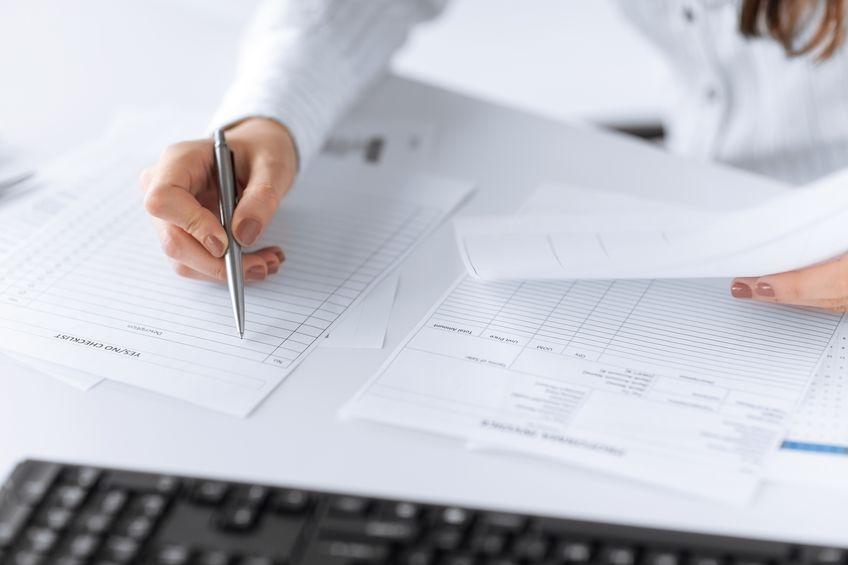 Frau, die mit der rechten Hand ein leeres Buchhaltungs-Formular ausfüllt für einfachere Kassenbuchhaltung