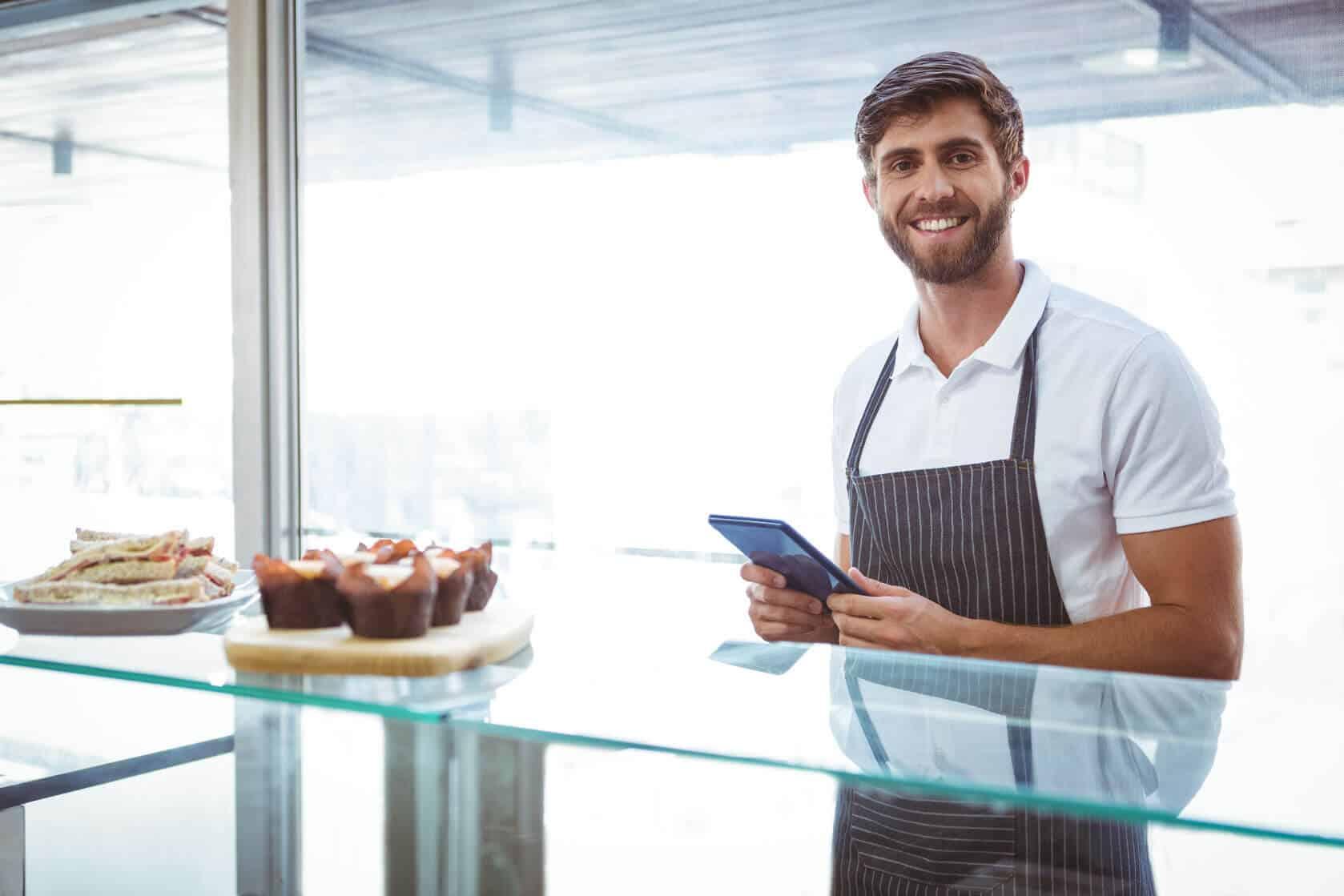 fröhlicher Mann vor einer Glastheke in einem Gastronomie-Unternehmen, arbeitet mit dem Kassensystem von GastroSoft