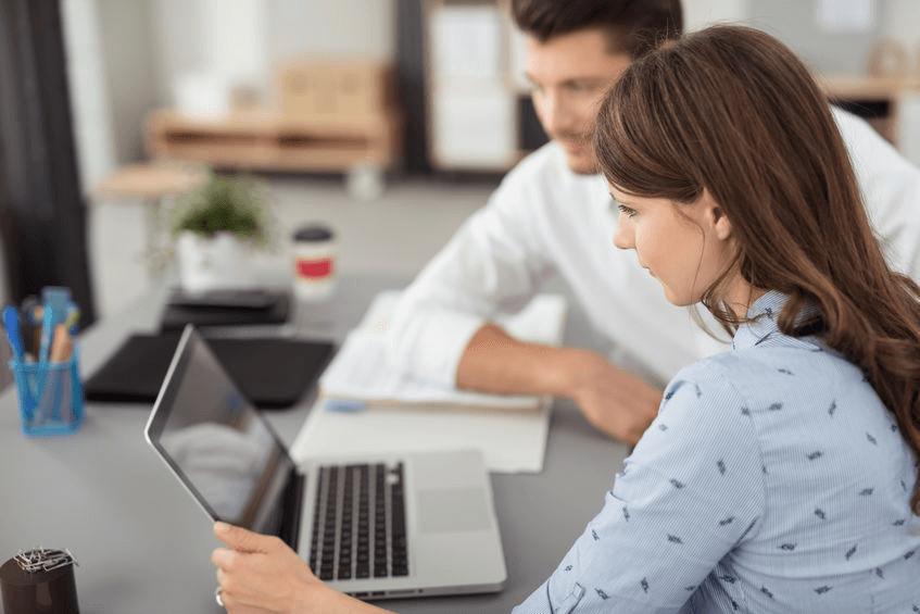 Zwei junge Unternehmer in einem Büro - Mann und Frau an einem Notebook - PosSoft Shop an der Kassensoftware des Kassensystems
