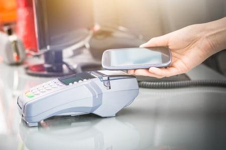 Kartenzahlungen mit blauem Hintergrund, Person mit Smartphone zahlt an einem mobilen Terminal, im Hintergrund ein Monitor