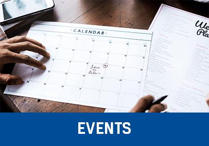 Kalender auf Papier mit Events die über die Event Erweiterung geplant wurden, im Hintergrund auf dem Tisch ein Smartphone