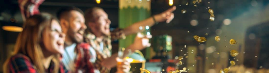 Freunde beim Biertrinken in einer Bar, freuen sich über ein Ereignis - das Event Add-On mit Kassensystem RFID von GastroSoft