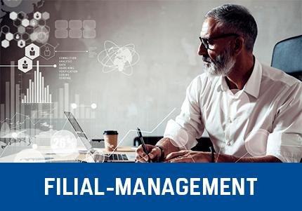Mann im weißen Hemd macht das Filial Mangement, vor ihm ein Notebook, Tisch und Kaffee und schwebende Icons für Management