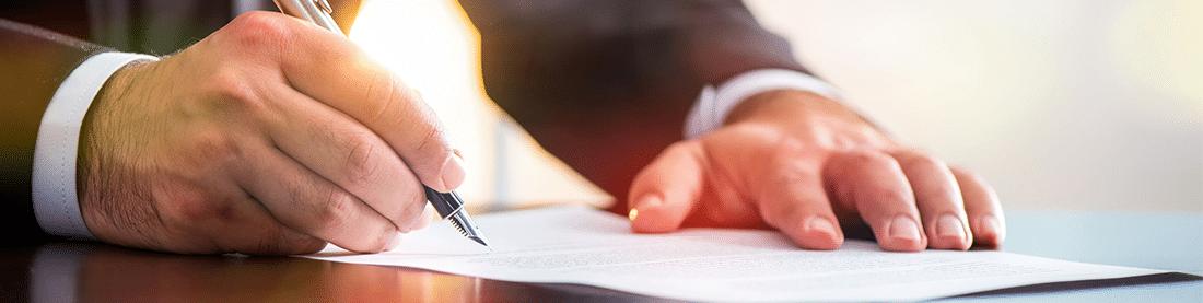 Mann im Anzug der mit einem Füller auf einen Blatt Papier schreibt, Finanzamt-konforme Kassensoftware mit GastroSoft