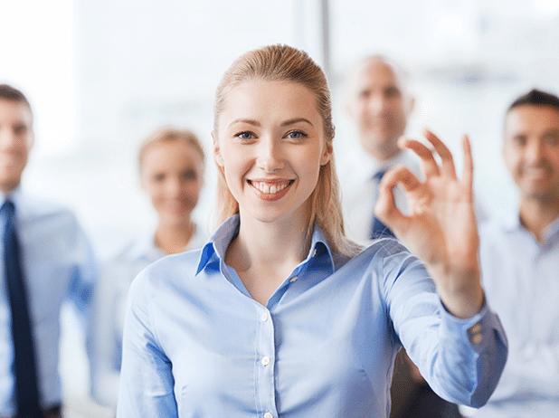 Glückliche Frau strahlt und hält die Hand mit Exzellent-Zeichen in die Kamera. Sie ist sehr zufrieden mit Ihrem GastroSoft CLUB Platin, der Mietversion der professionellen Kassensystemlösungen