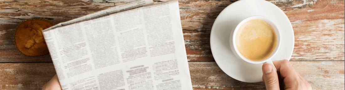 Person mit Zeitung und Kaffee am Holztisch - GastroSoft News, Blog und Newsletter über Kassenprodukte und Kassensysteme