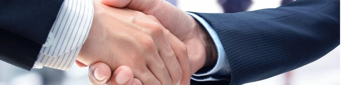 GastroSoft und Vertriebspartner oder Partner schütteln sich die Hand beide sind Profis und tragen Anzüge