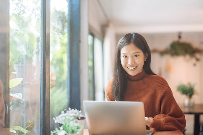 Frau vor ihrem Computer, sie ist glücklich mit Ihrem GastroSoft Lieferdienst Online-Shop