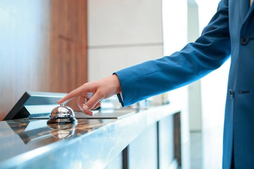 Hotel Add-On Kassensoftware Erweiterung: Person im blauen Jacket an einer Hotel-Rezeption läutet die Tischglocke am Tresen