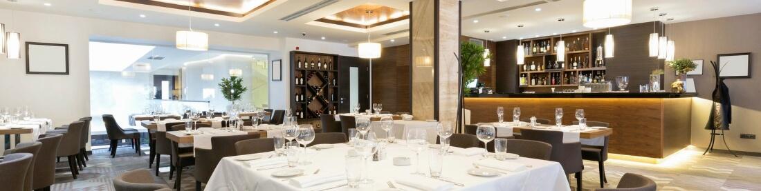 Hotel Restaurant mit gedeckten Tischen und Bar welche mit der Hotel Software Add-On Erweiterung der Kassensoftware arbeiten
