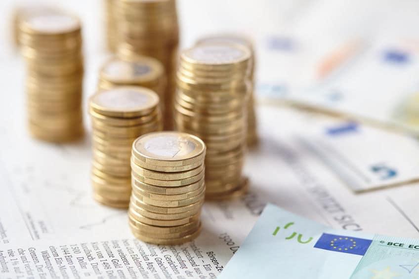 mehrere Stapel Euromünzen und Euroscheine auf einer Zeitung stehend für das Kassenbuch Add-On der Kassensoftware Erweiterung