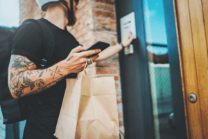 Mann mit Helm auf dem Kopf, Smartphone und Tüte in der Hand klingelt an Tür: Lieferdienst Add-On Kassensoftware Erweiterung