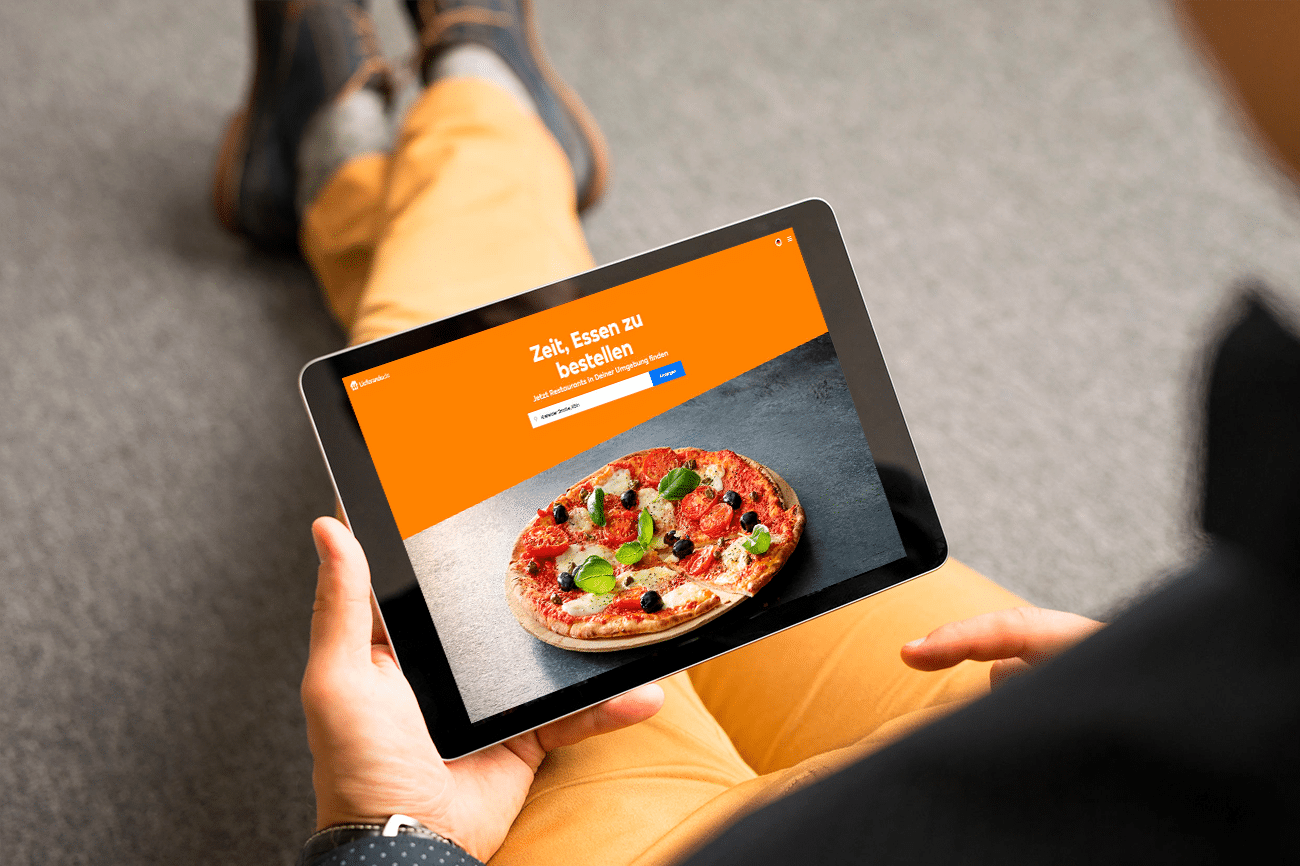 Person am Tablett bestellt, Online-Shop der Kassensoftware Erweiterung, Online-Lieferdienst Add-On von GastroSoft