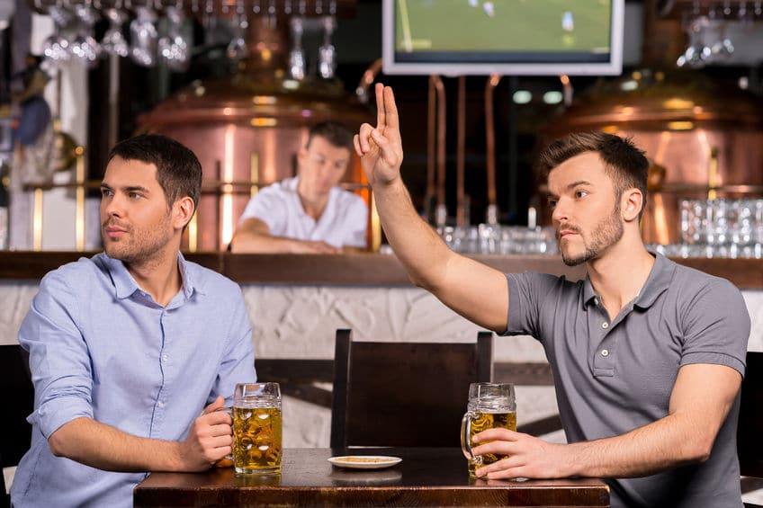 Zwei Männer mit Bier sitzend in einer Bar - einer ruft den Kellner, Schankmanagement Add-On Erweiterung der Kassensoftware