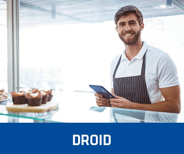 fröhlicher Mann vor einer Glastheke einer Gastronomie, arbeitet mit dem Kassensystem Droid Support für mobile Bestellösungen