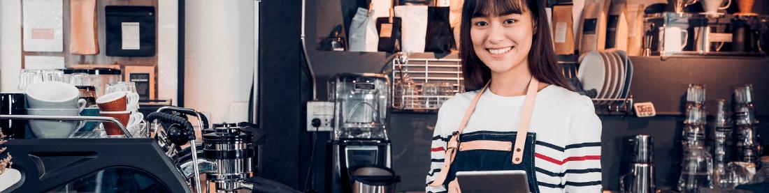 braunhaarige Frau im weiß-gestreiften pullover in einem Cafe als Kellnerin oder Barista stehend für mobile Bestellterminals
