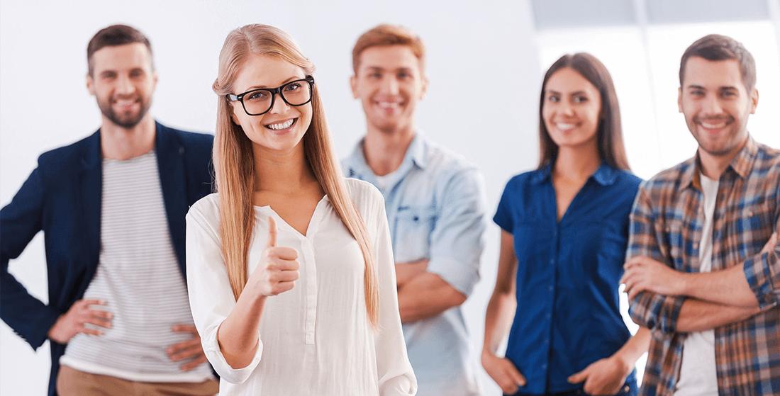 TSE-Stark: vier glückliche Personen im Hintergrund eine blonde fröhliche Frau vorne die ihren Daumen nach oben zeigt - TSE Kassensystem