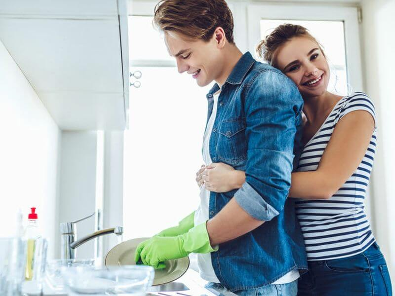 glücklicher Mann im blauem Jeanshemd der den Abwasch macht und fröhliche Frau die ihn dabei umarmt: KassenSichv 2020