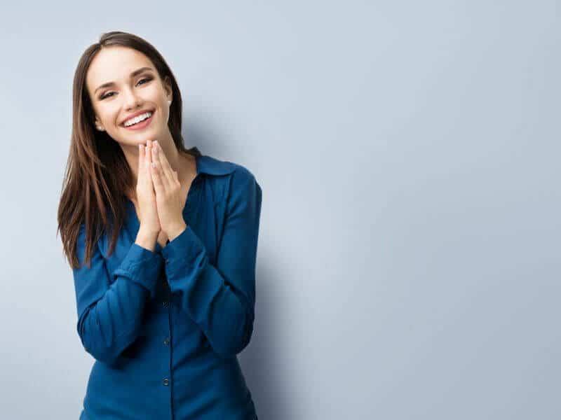 lächelnde Frau mit braunen Haaren und blauer Bluse zufrieden über ihren Ansprechpartner bei GastroSoft