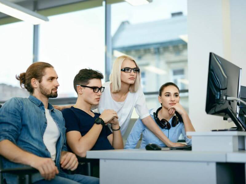 zwei Männer und zwei Frauen an einem Computer schauen sich das Finanzamtkonforme (KassenSichv 2020) Kassensystem an