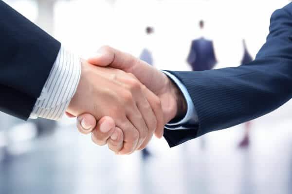 Helles Bild - GastroSoft und Vertriebspartner oder Partner schütteln sich die Hand beide sind Profis und tragen Anzüge