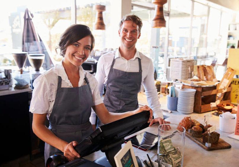 Mann und Frau glücklich mit ihrem Kassensystem, Kassensoftware Lösung Komplettpaket von GastroSoft