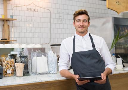Mann braune Haare, schwarzer Schürze und weißem Hemd vor einer Theke in einer Gastronomie mit einem Tablet Kassensystem