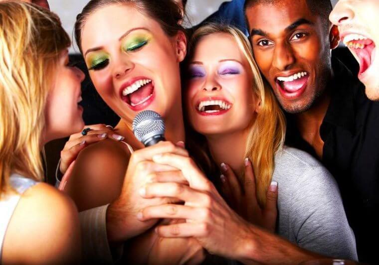 Singende Freunde, drei Frauen, zwei Männer, Mikrofon in den Händen